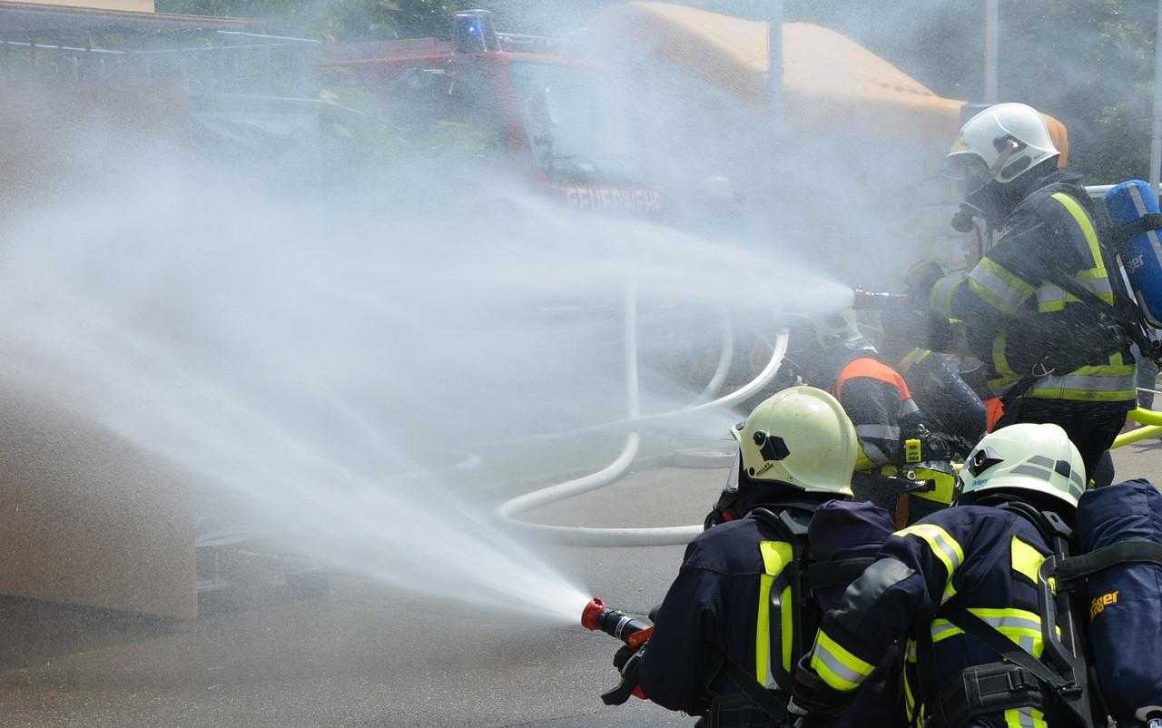 Feuerwehrmänner, die dicht nebeneinander stehen und mit dem Löschschlauch Wasser verspritzen.